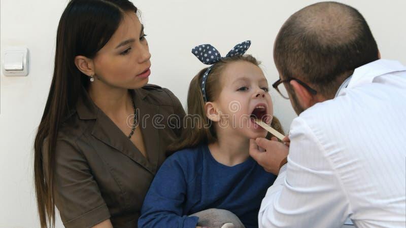 Bambina che ha esame della gola da un medico maschio fotografia stock libera da diritti