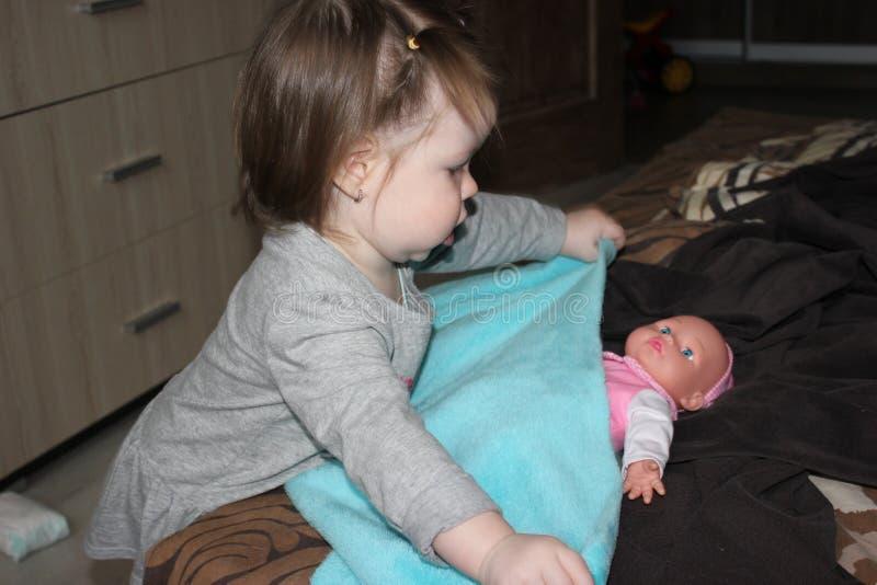 Bambina che harboring con attenzione una bambola immagini stock libere da diritti