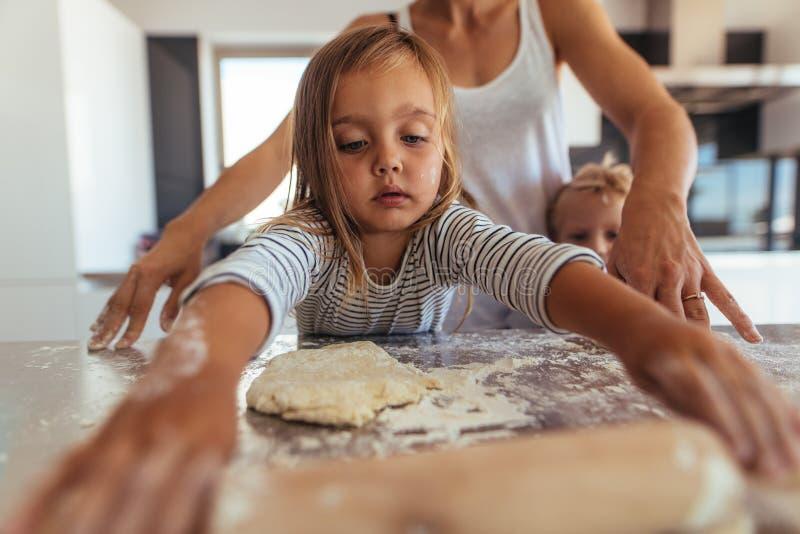 Bambina che impara cottura e cuocere immagini stock libere da diritti