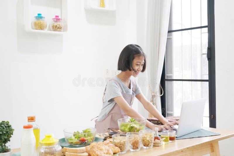 Bambina che impara online cottura con utilizzare computer portatile nella cucina immagine stock libera da diritti