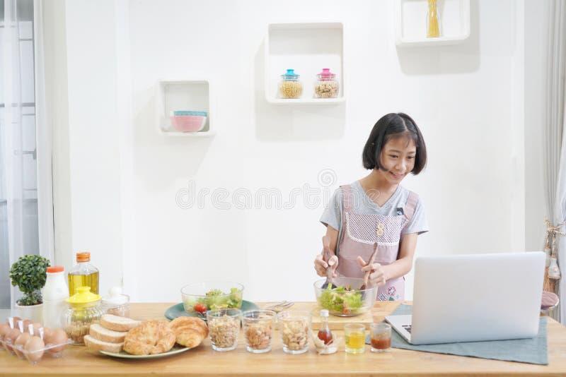 Bambina che impara online cottura con utilizzare computer portatile nella cucina fotografia stock libera da diritti
