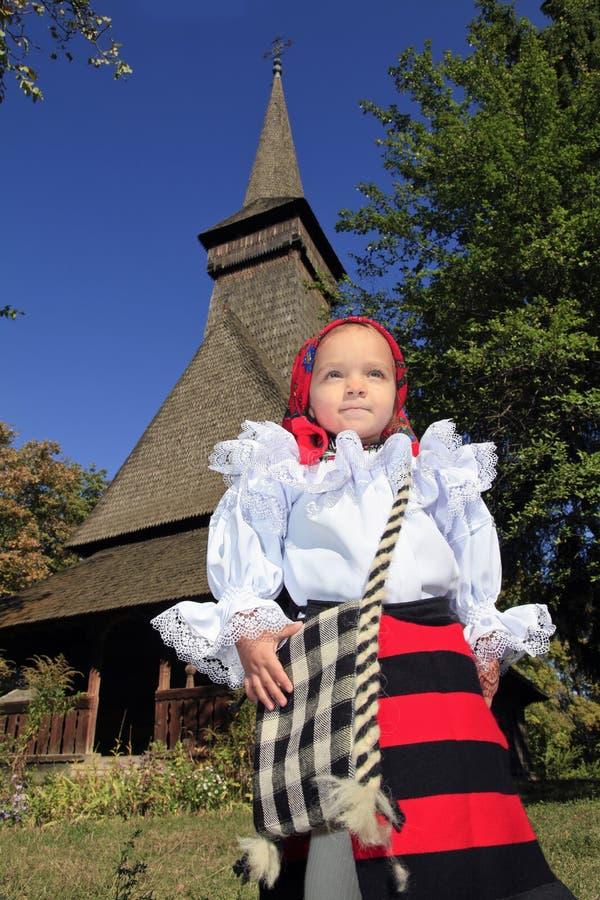 Bambina che indossa abbigliamento tradizionale rumeno e chiesa di legno tradizionale su un fondo immagine stock