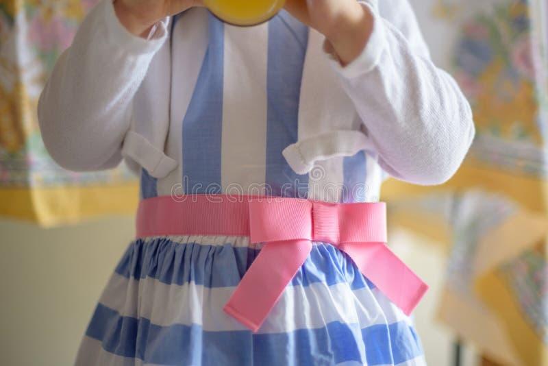 Bambina che indossa il vetro del succo della tenuta del vestito da Pasqua immagini stock libere da diritti