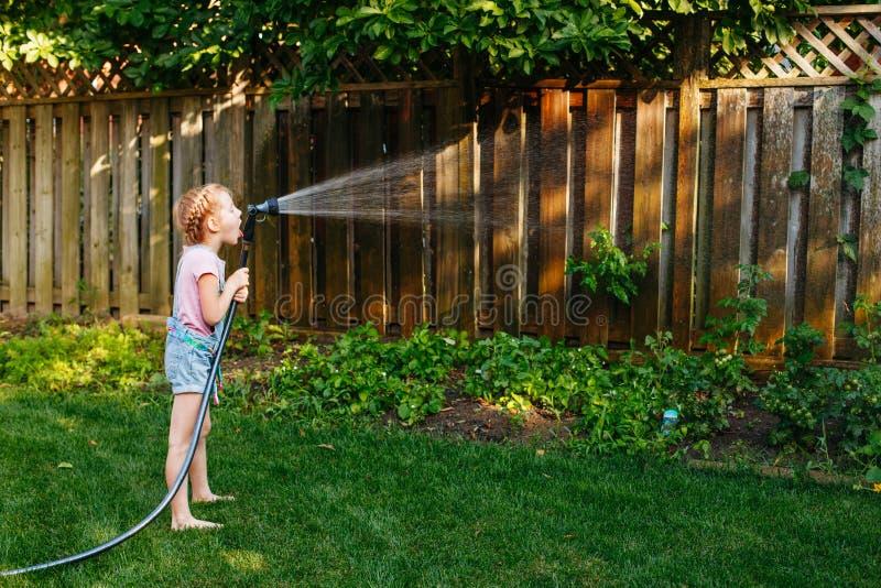 Bambina che innaffia le piante verdi sul cortile fotografie stock