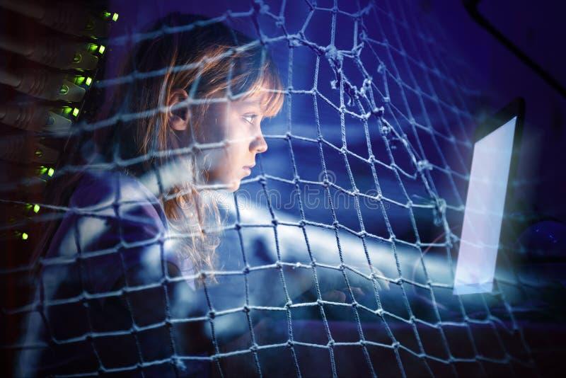 Bambina che lavora al computer portatile alla notte in una rete da pesca fotografia stock libera da diritti