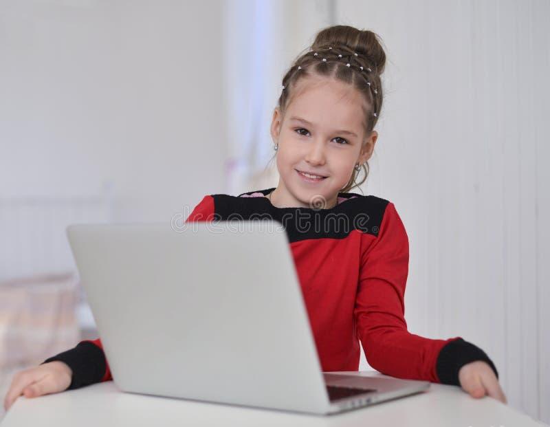 Bambina che lavora al computer portatile che si siede alla tavola fotografie stock libere da diritti