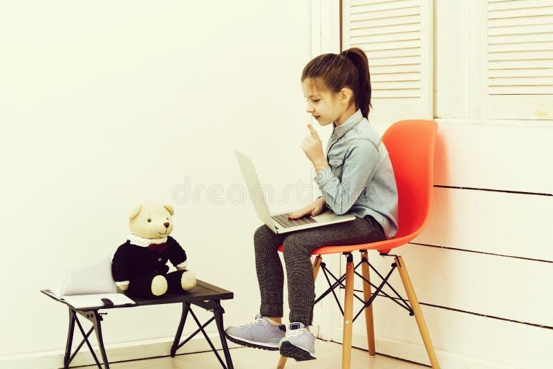 Bambina che lavora al computer portatile con l'orsacchiotto immagine stock libera da diritti