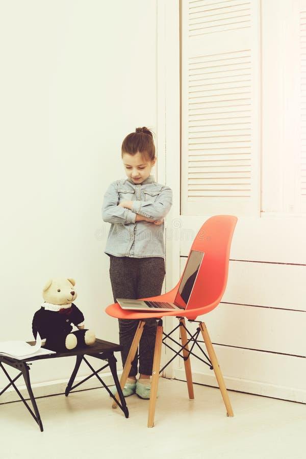 Bambina che lavora al computer portatile con l'orsacchiotto fotografia stock