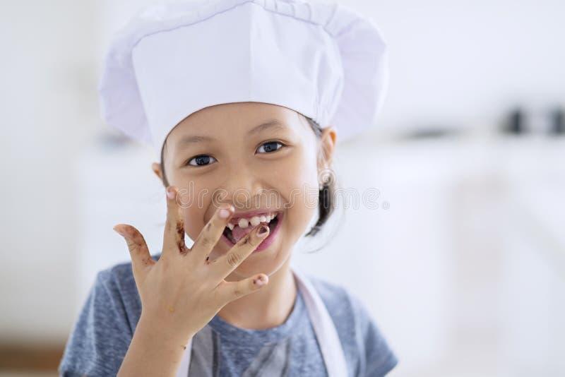 Bambina che lecca cioccolato sul suo dito fotografia stock