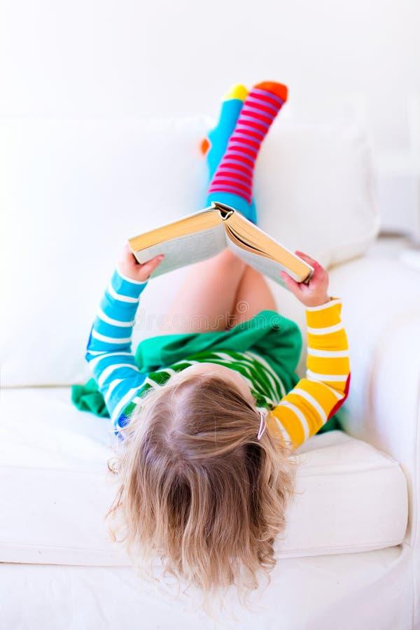 Bambina che legge un libro su uno strato bianco fotografie stock libere da diritti