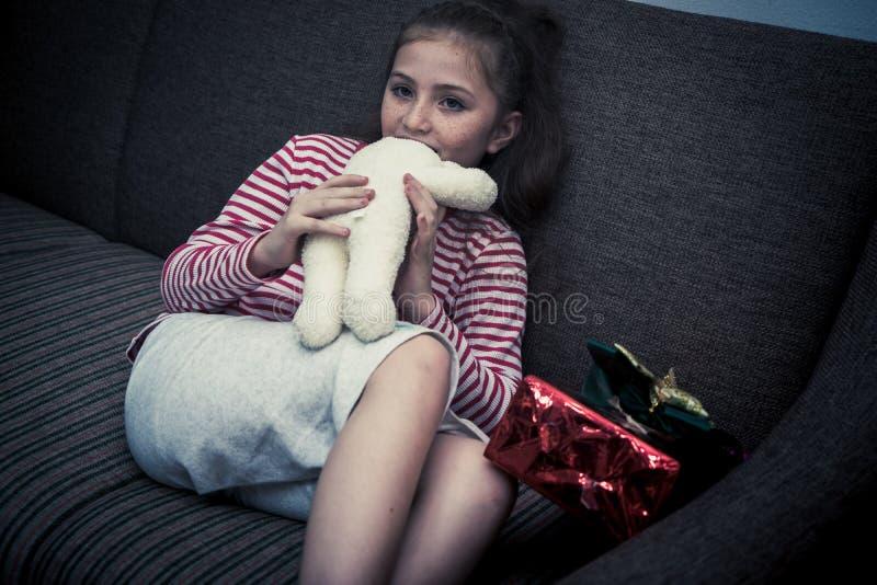 Bambina che mangia bambola nell'angolo scuro della stanza fotografia stock libera da diritti