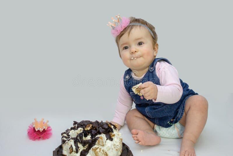 Bambina che mangia dolce, dieci mesi, grande dolce per la festa immagini stock