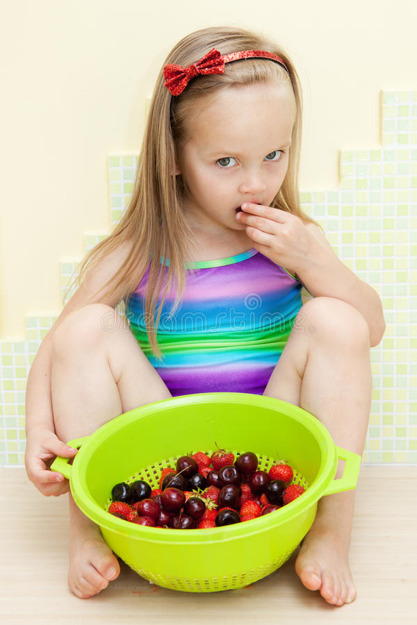 Bambina che mangia frutta fotografie stock libere da diritti