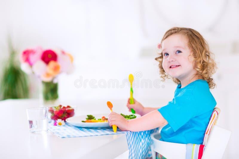 Bambina che mangia insalata per pranzo fotografie stock