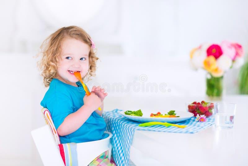 Bambina che mangia insalata per pranzo fotografia stock