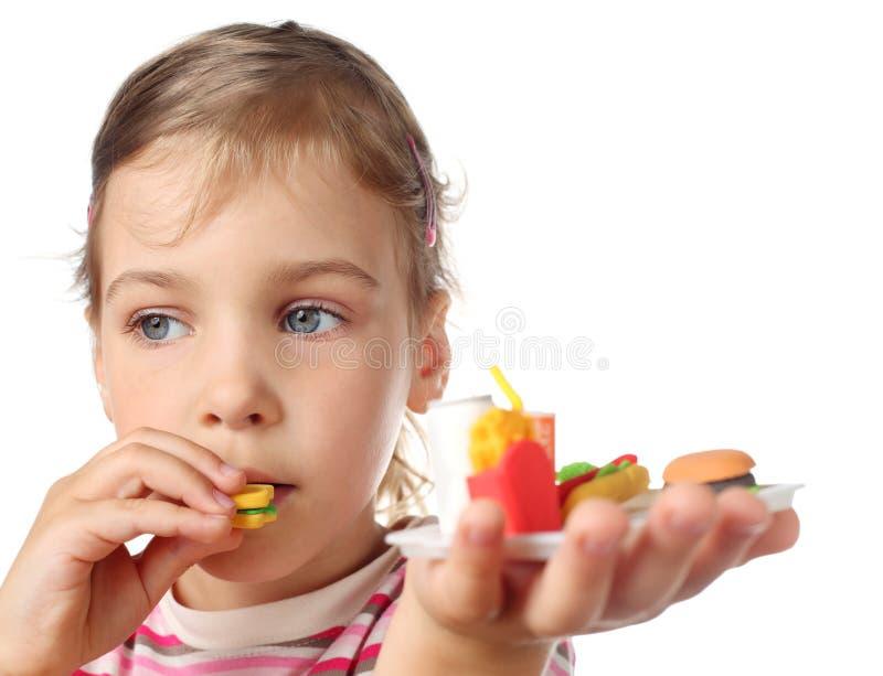 Bambina che mangia l'hamburger della miniatura del giocattolo immagini stock libere da diritti