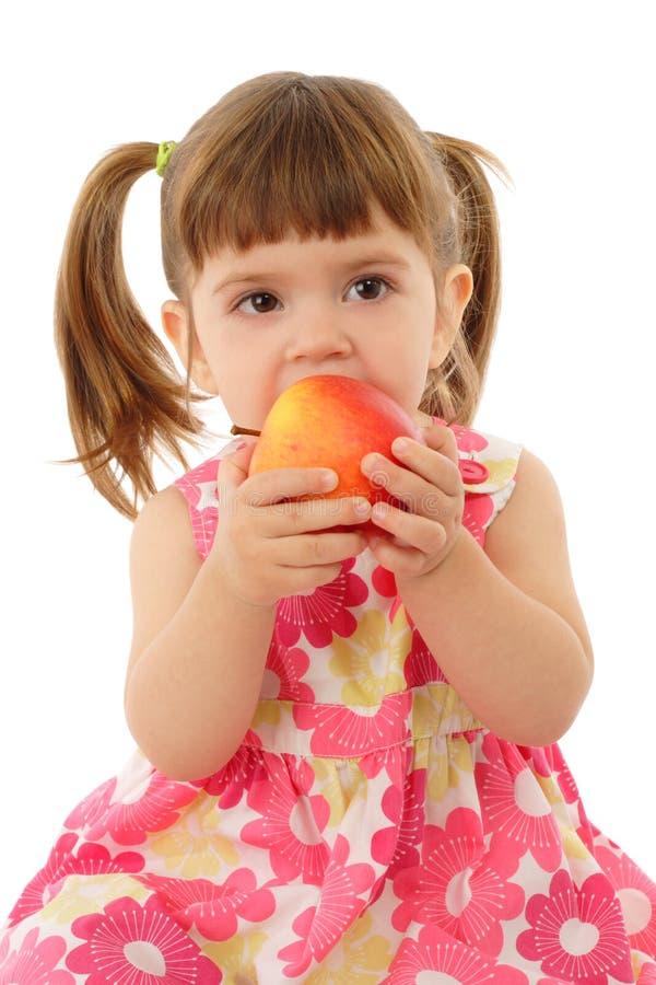 Bambina che mangia mela gialla fotografia stock libera da diritti