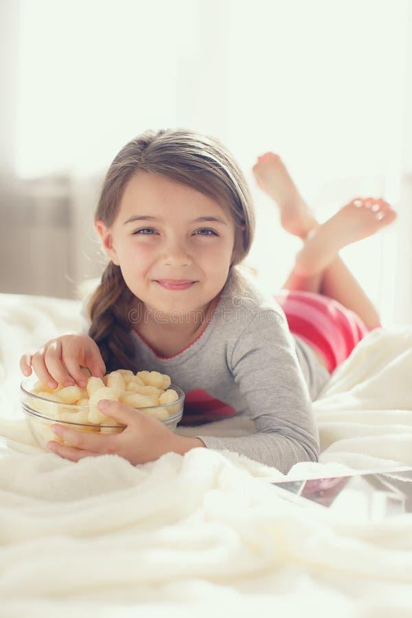 Bambina che mangia popcorn a letto fotografie stock libere da diritti