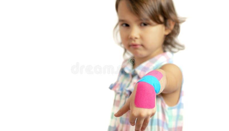 Bambina che mostra il suo polso bendato con nastri adesivi di kinesio fotografia stock libera da diritti