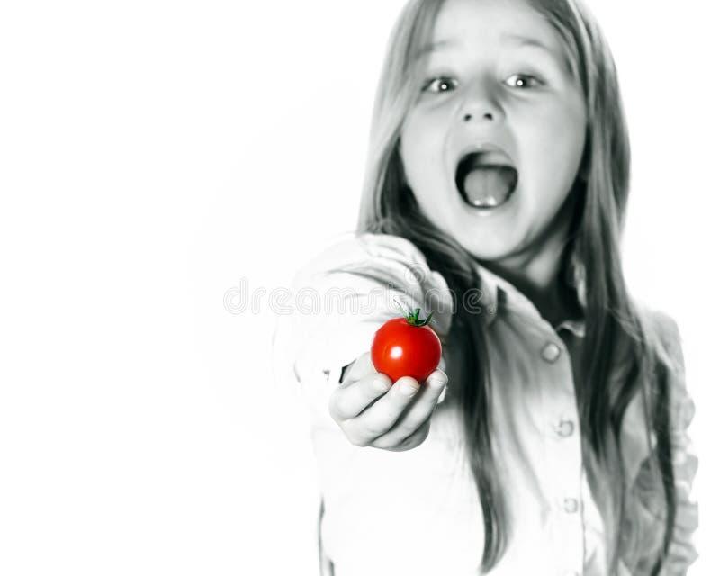 Bambina che mostra piccolo pomodoro rosso fotografia stock