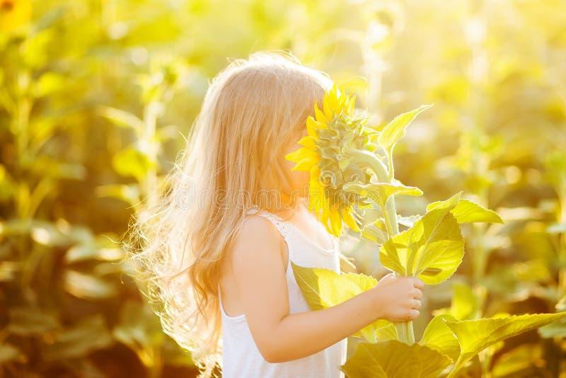 Bambina che odora un girasole immagini stock libere da diritti