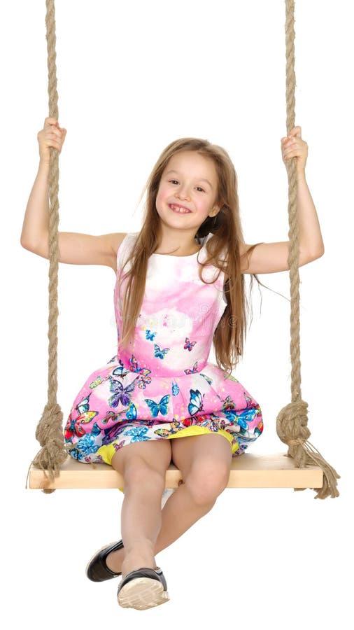 Bambina che oscilla su un'oscillazione fotografia stock libera da diritti