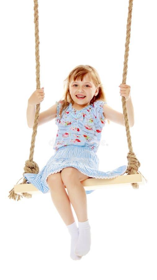 Bambina che oscilla su un'oscillazione fotografia stock