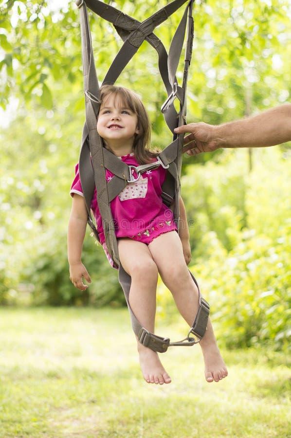 Bambina che oscilla sulle cinghie di un paracadute immagini stock libere da diritti