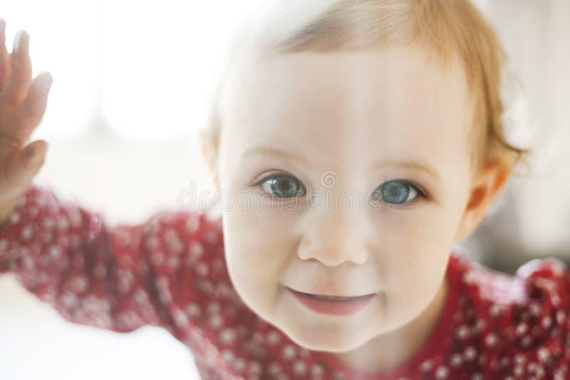 Bambina che osserva attraverso il vetro immagini stock libere da diritti