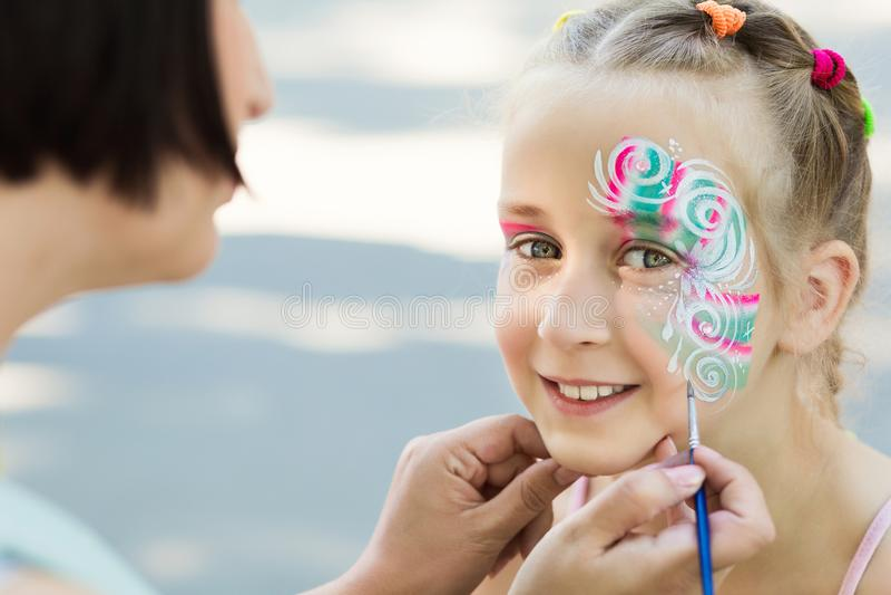 Bambina che ottiene il suo fronte dipinto dall'artista della pittura del fronte immagini stock