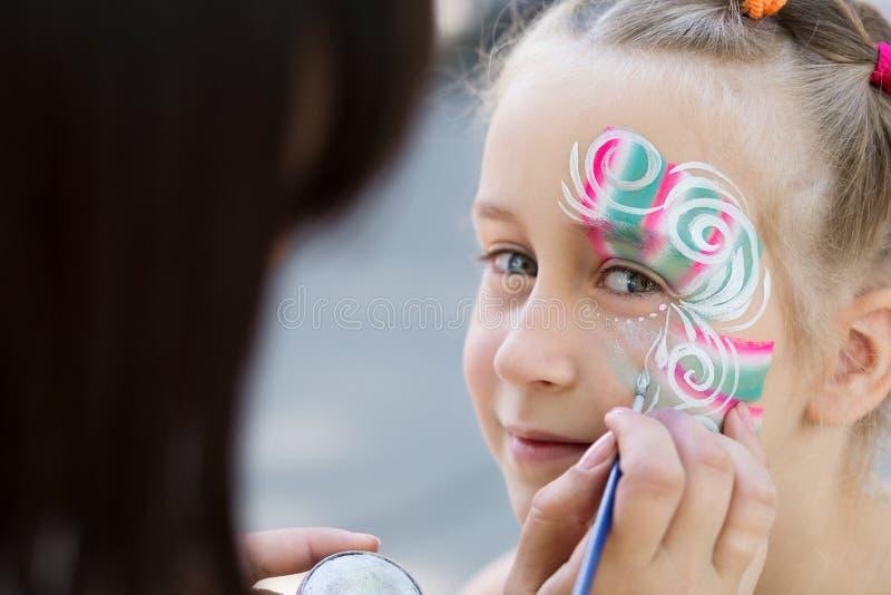 Bambina che ottiene il suo fronte dipinto dall'artista della pittura del fronte immagine stock libera da diritti