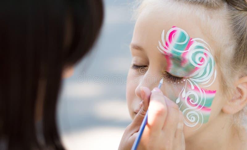 Bambina che ottiene il suo fronte dipinto dall'artista della pittura del fronte fotografie stock libere da diritti