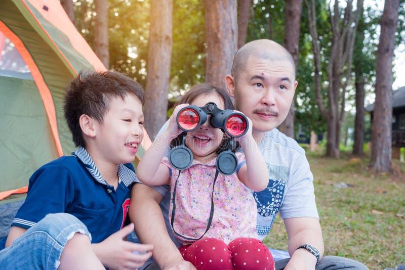 Bambina che per mezzo del binocolo con la sua famiglia immagine stock libera da diritti