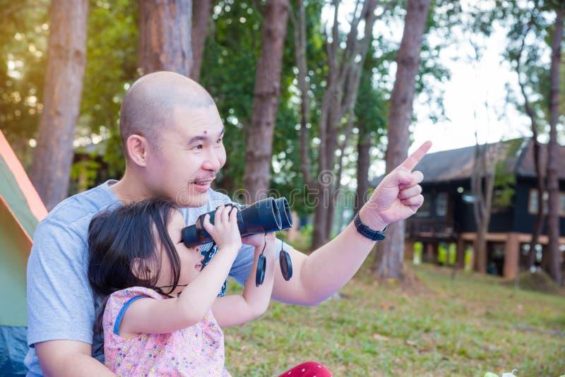 Bambina che per mezzo del binocolo con suo padre immagini stock