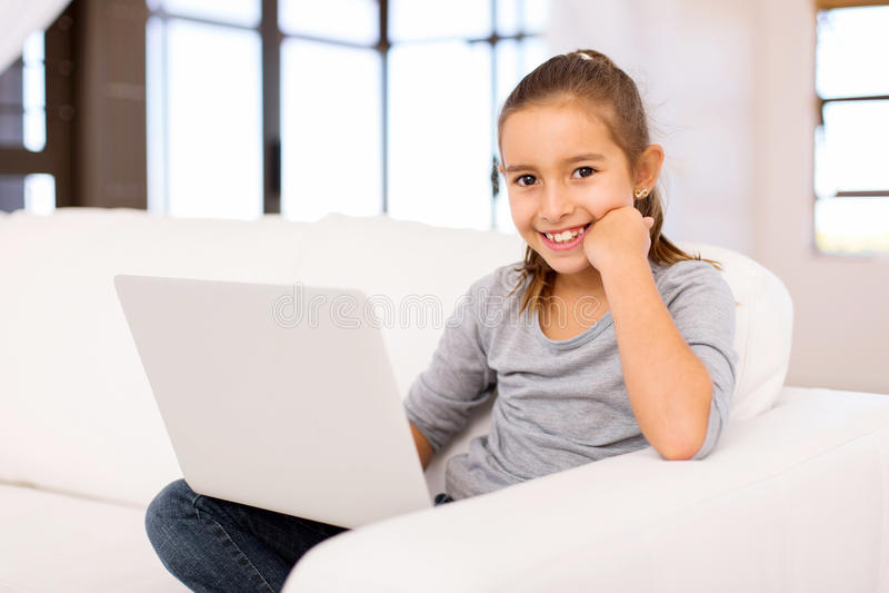 Bambina che per mezzo del computer portatile fotografia stock
