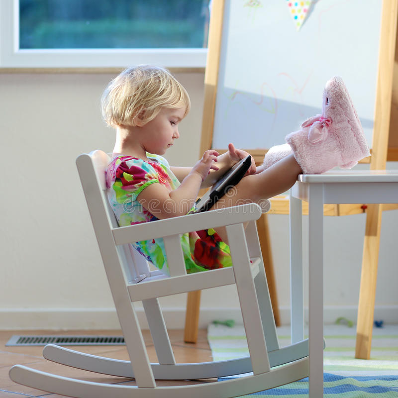 Bambina che per mezzo del pc della compressa a casa immagini stock