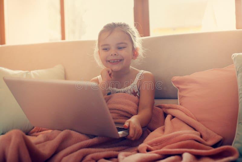 Bambina che per mezzo del suo computer portatile immagini stock libere da diritti
