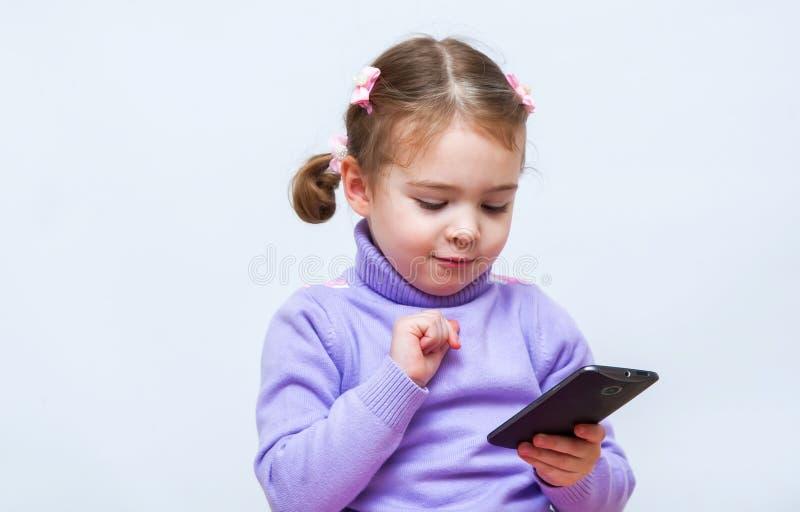 Bambina che per mezzo dello Smart Phone fotografie stock libere da diritti