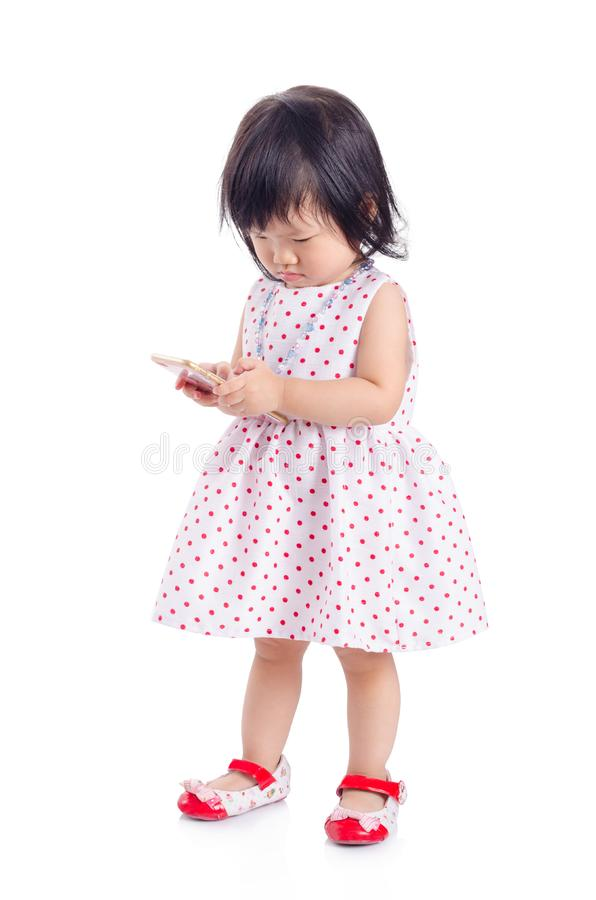 Bambina che per mezzo dello Smart Phone sopra bianco immagini stock libere da diritti