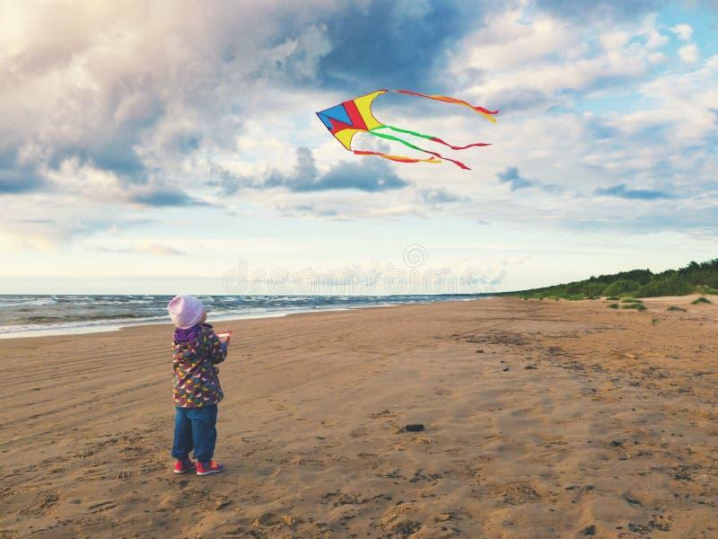 Bambina che pilota un aquilone sulla spiaggia al tramonto fotografia stock libera da diritti