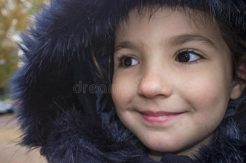 Bambina che porta il cappotto blu scuro di inverno con il cappuccio della pelliccia del faux fotografie stock