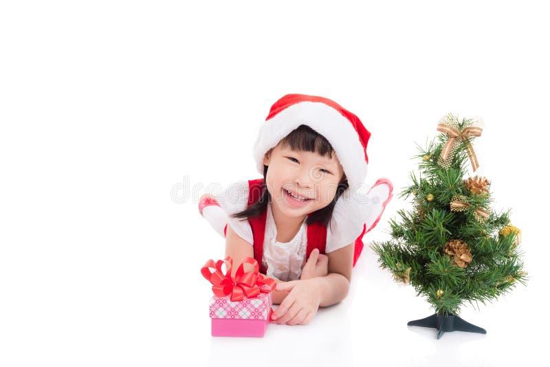 Bambina che porta il vestito da Santa che si trova sul pavimento fotografie stock libere da diritti