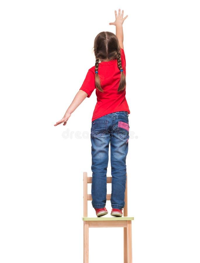 Bambina che porta maglietta rossa e che raggiunge fuori qualcosa su ciao fotografia stock