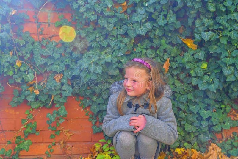 Bambina che porta retro cappotto e che si accovaccia davanti al muro di mattoni in autunno Parete dell'edera in autunno Concetto  immagine stock
