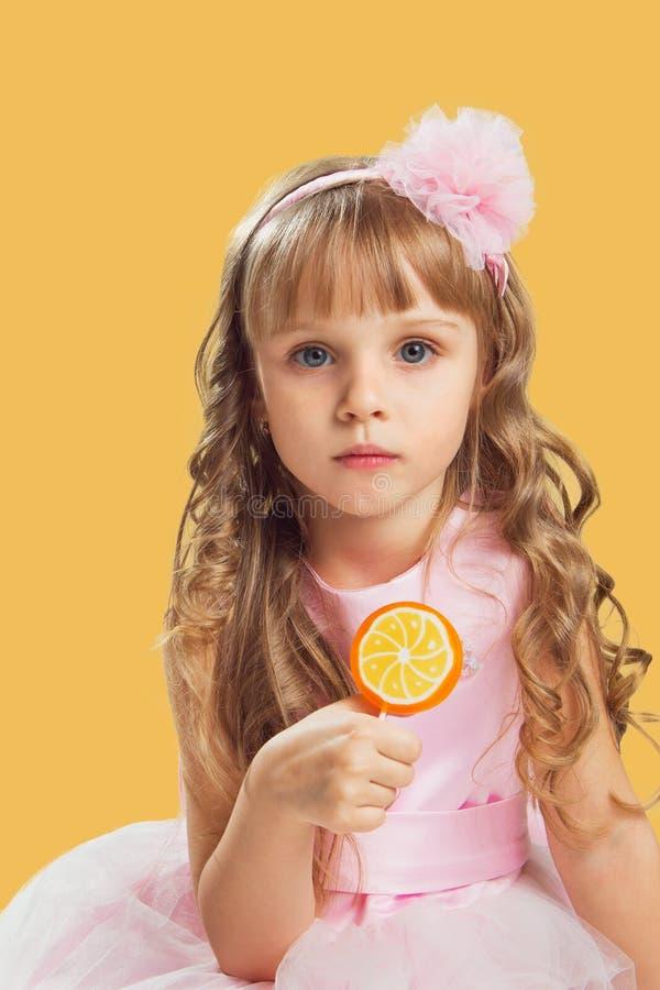 Bambina che posa in uno studio sopra il fondo di colore Tenuta della a immagine stock