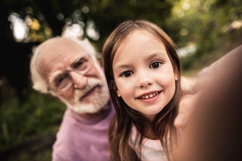 Bambina che prende selfie con suo nonno fotografia stock libera da diritti
