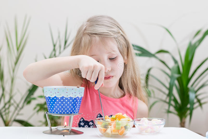 Bambina che prepara e che mangia una fonduta di cioccolato fotografia stock