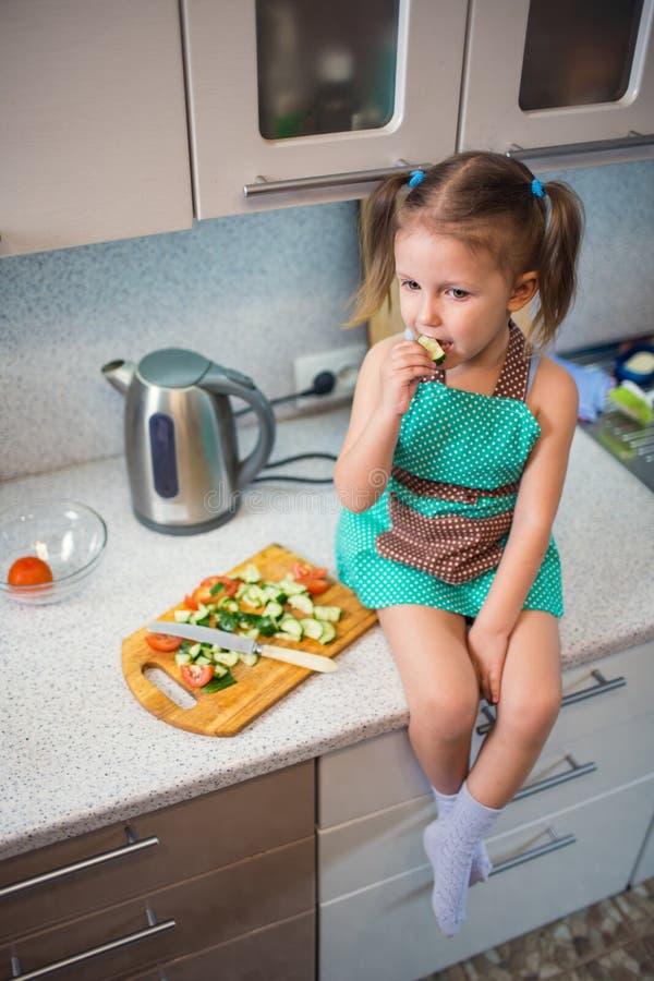 Bambina che prepara insalata nella cucina immagini stock