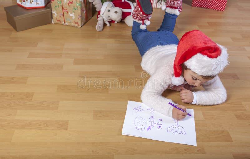 Bambina che prepara Santa Letter Lei che dipinge i regali s fotografie stock