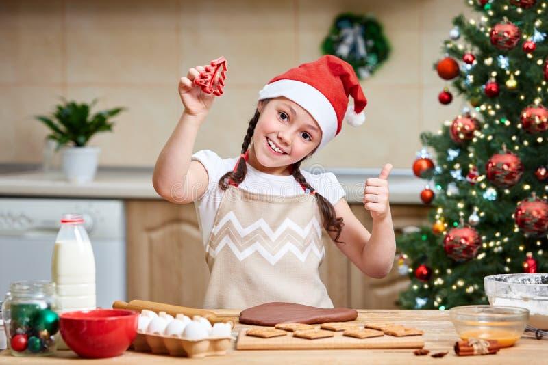 Bambina che produce pan di zenzero Preparazione per natale immagini stock